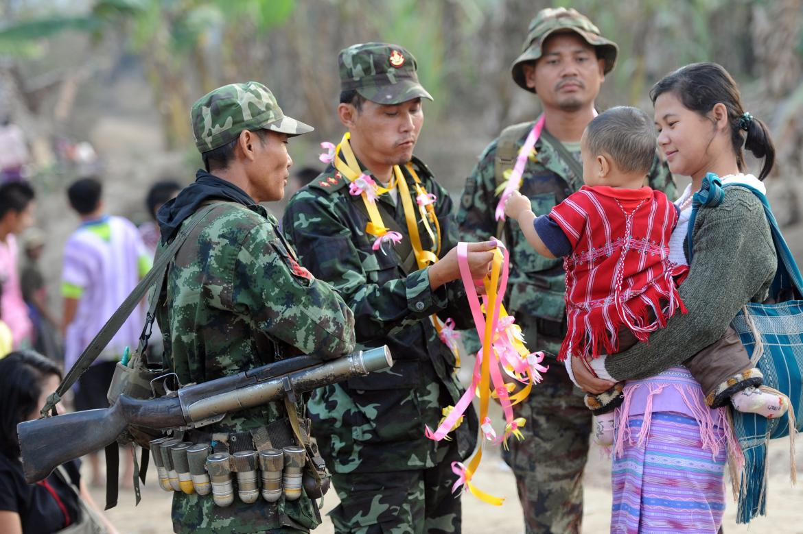 Soldiers from the Karen National Union greet a local mother and her child.