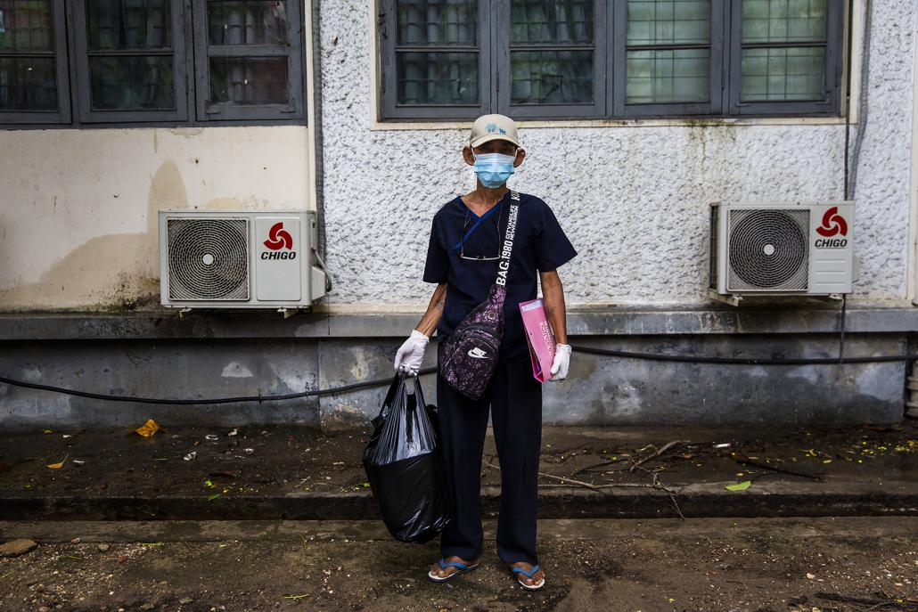 A medical worker arrives at the National Health Laboratory in Yangon on May 10 carrying a sample he has brought from Bago Region for testing. (Hkun Lat | Frontier)