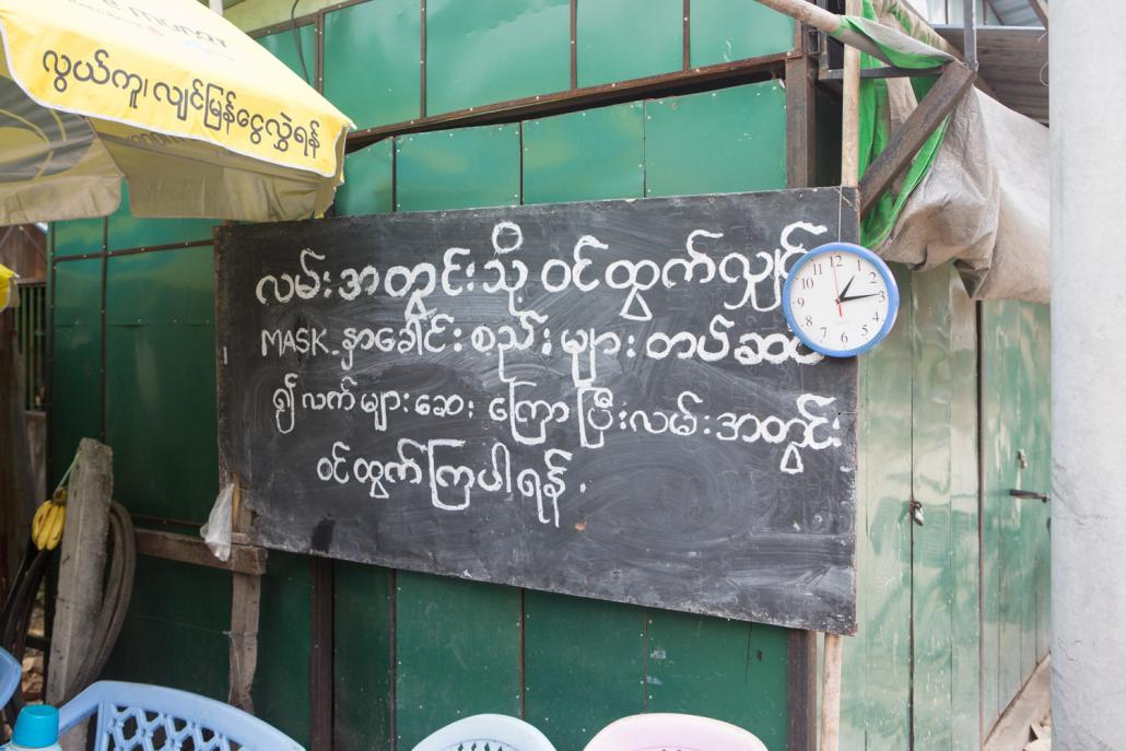 A signboard warns people to wear facemasks and wash their hands before entering the street. (Thuya Zaw | Frontier)
