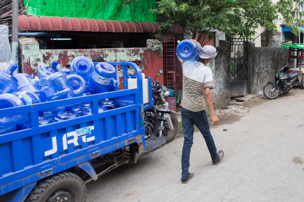 Small armies of workers deliver drinking water to homes and businesses each day, making them prime candidates for catching and spreading COVID-19. (Thuya Zaw | Frontier)