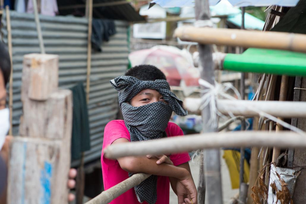A boy uses a longyi as a facemask in Insein Township's West Ywar Ma ward. (Thuya Zaw | Frontier)