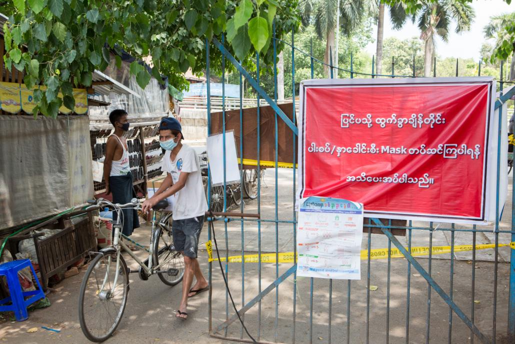 Residents of some wards in Insein Township have set up roadblocks and signboards warning people to wash their hands and wear facemasks. (Thuya Zaw | Frontier)