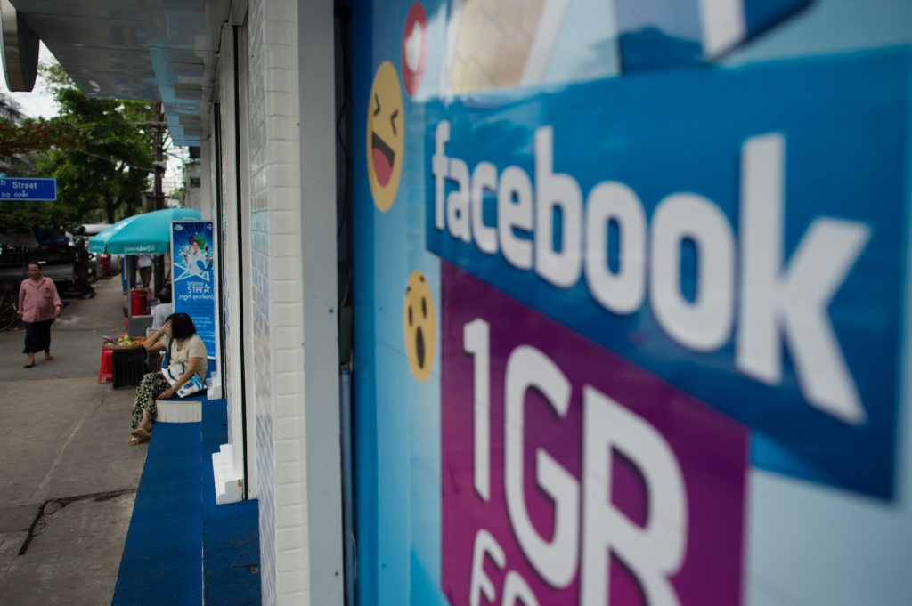 The Facebook logo is seen on an advertisement by a telecom company in Yangon in June 2018. (AFP)