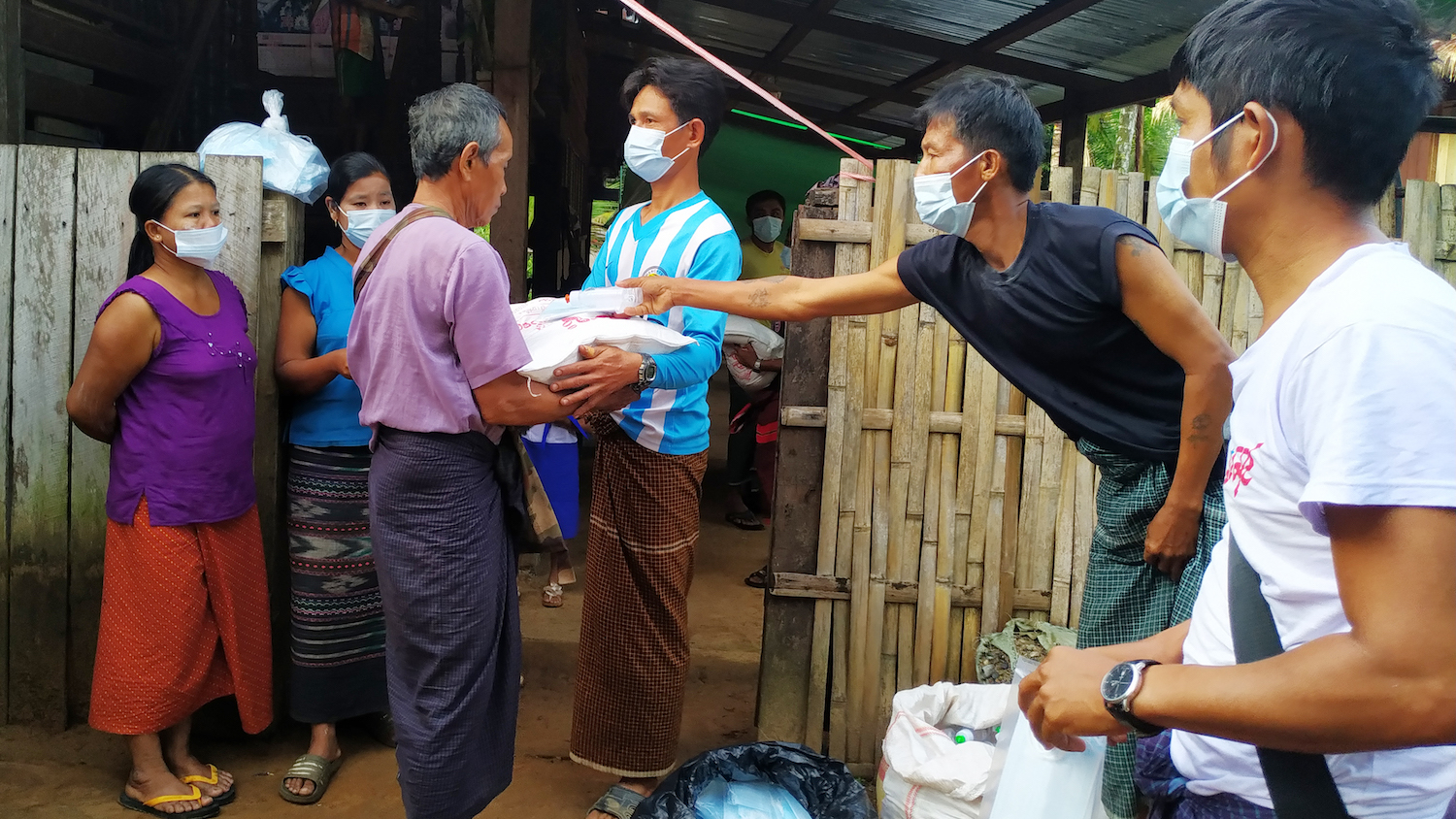 Members of the Mon Area Community Development Organization distribute bags of rice and health and hygiene items in Gani IDP site in eastern Ye township, Mon State, in early May. (Supplied | HURFOM)