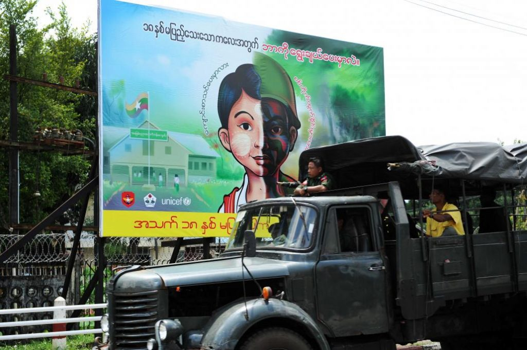 A Tatmadaw truck passes by a public sign stating that only people aged 18 or above can enlist in the military. (Steve Tickner   Frontier)