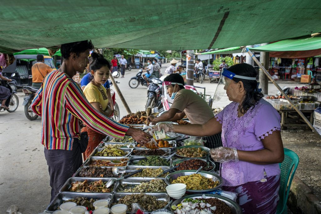 Food vendors wear field shields while serving customers in Mrauk-U, a week before the government ordered a state-wide stay-at-home order to prevent the spread of COVID-19. (Hkun Lat | Frontier)