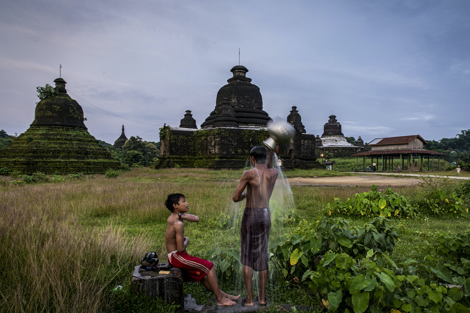 Children shower near a pagoda in Mrauk-U, Rakhine State on 21 August 2020. (Hkun Lat I Frontier)