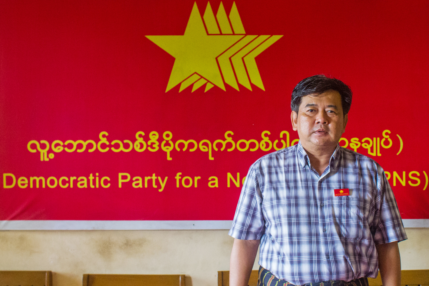 Longtime democracy activist and chair of the Democratic Party for a New Society U Aung Moe Zaw stands before a party signboard. (Mar Naw | Frontier)