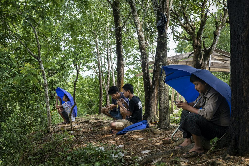Mrauk-U residents sit atop a forested hill just outside of town trying to get a 3G cell phone signal. Internet has been blocked by the government there for more than year. (Hkun Lat | Frontier)