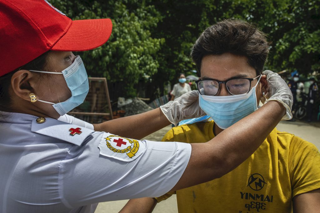 A Red Cross officer adjusts a man's mask in Mrauk-U on August 21. (Hkun Lat | Frontier)