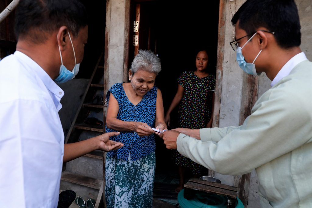 A Dawbon Township resident receives K20,000 from a local administrator under the government's cash transfer programme on July 25. (Nyein Su Wai Kyaw Soe | Frontier)