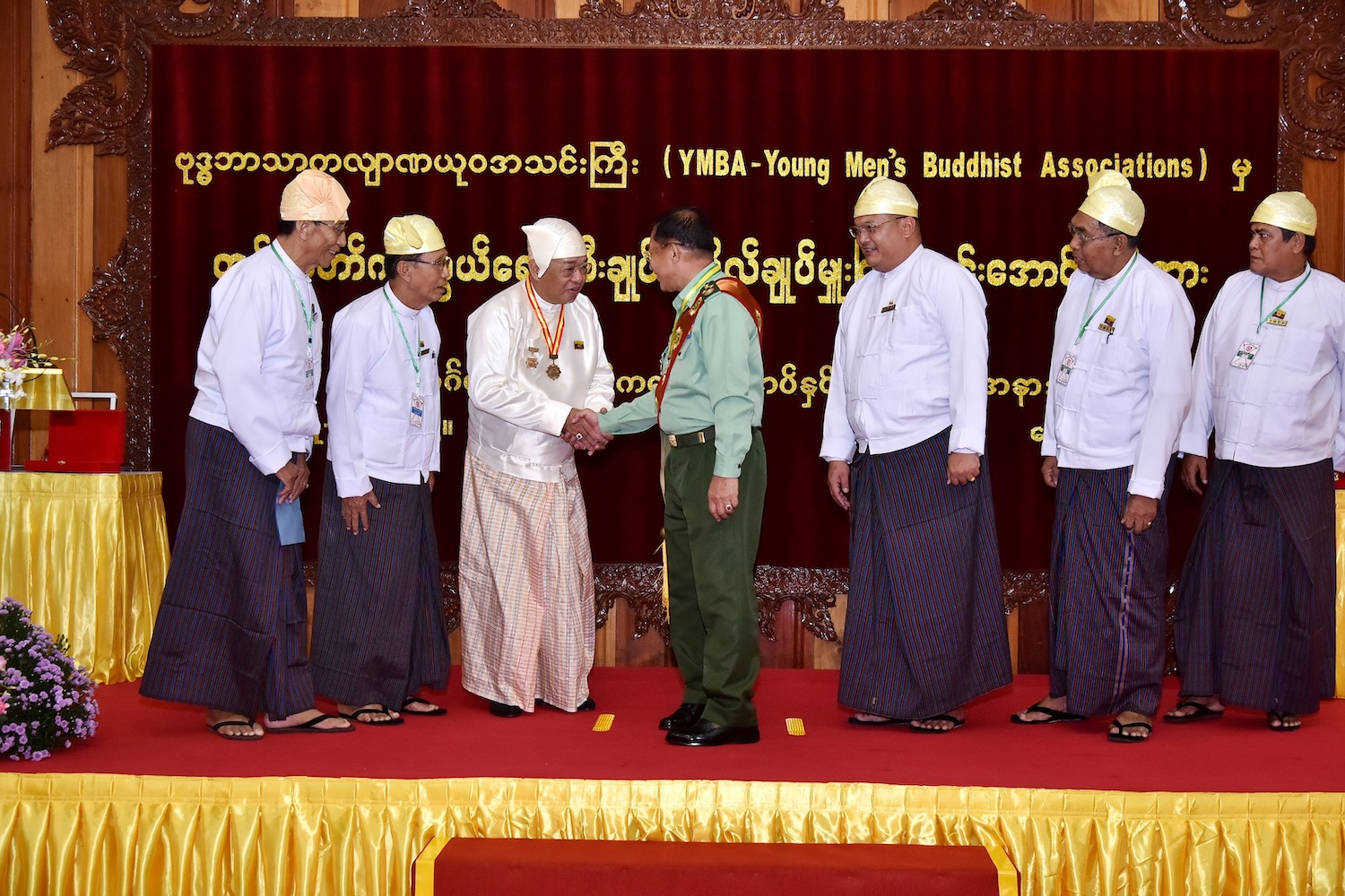 YMBA chair U Ye Htun shakes Senior General Min Aung Hlaing's hand after presenting him with an award and making him the group's patron for life in October 2019. (Supplied | CINDCS)