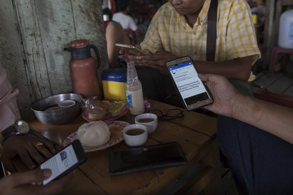 People gather at a Yangon teashop and browse Facebook on their mobile phones on August 31, 2018. (AFP)