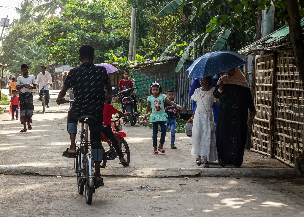 People walk along a street at the Aung Mingalar quarter for Rohingya Muslims as they observe the first day of the Eid al-Fitr holiday, which marks the end of the Islamic holy month of Ramadan, in Sittwe, Myanmar's Rakhine State on May 24, 2020. (Photo by - / AFP)