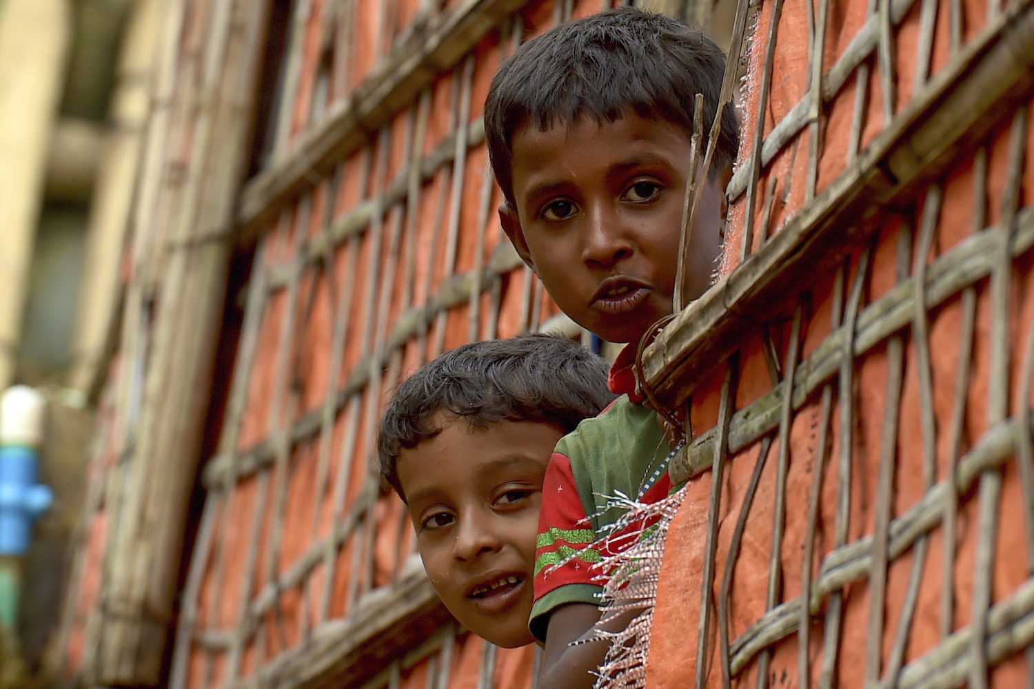 Rohingya refugee children look out from their shanty in Chakmarkul refugee camp in Teknaf on August 26, 2020. (AFP)