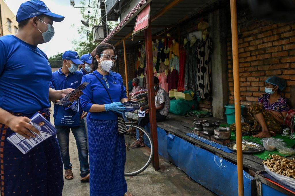 People's Pioneer Party chairperson Thet Thet Khine, right, gives out campaign literature to street vendors with other party members on September 8. (AFP)