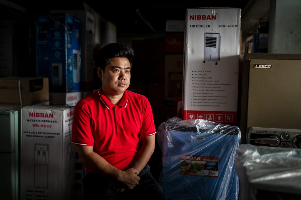 Lum Tu, 33, at his mobile and electronics shop in Myitkyina on July 21. (Hkun Lat)