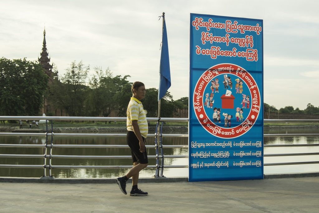 """A poster by the palace moat in Mandalay says, """"All native ethnic groups, let's vote to be responsible citizens."""" (Teza Hlaing 