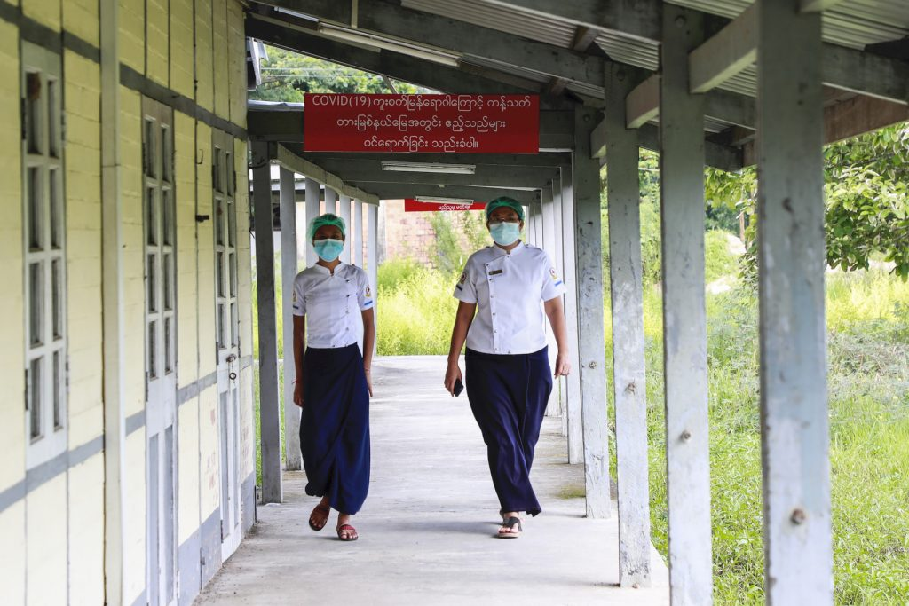 """Two nurses walk past a sign that reads """"no guests allowed, restricted area due to the spread of COVID-19"""" at a quarantine facility in Thingangyun Township on September 10. (Nyein Su Wai Kyaw Soe 