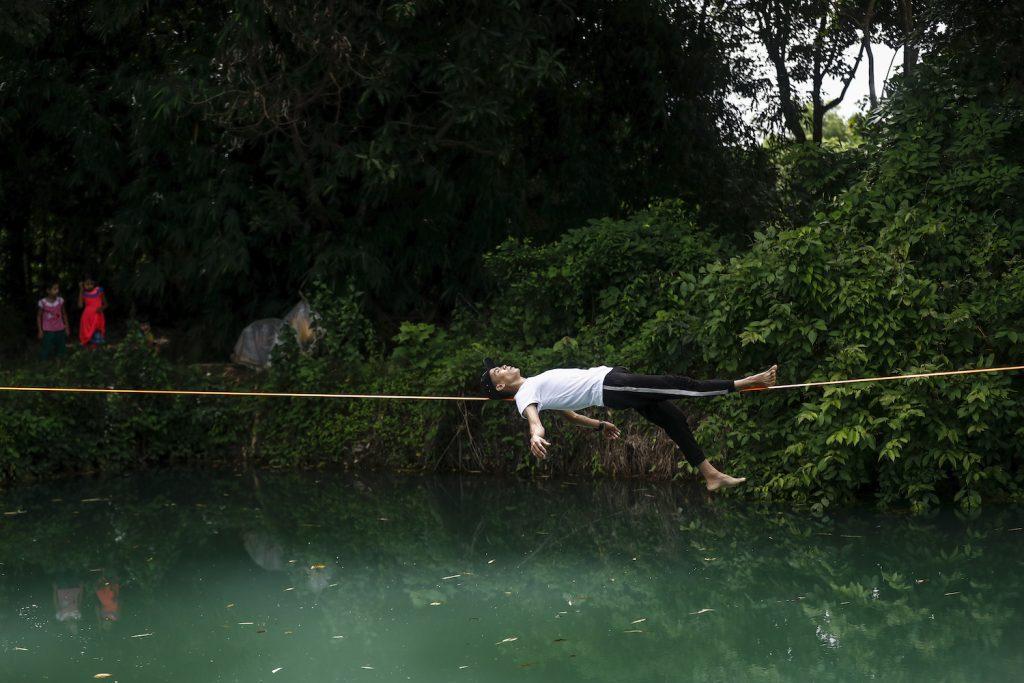 "Ko Ye Win Tun balances on a slackline above a pond – what practitioners call ""waterlining."" (Nyein Su Wai Kyaw Soe | Frontier)"