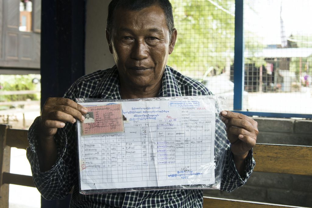 Two Muslim residents of Sintgaing Township's Khanluu village, a man aged 57 and a boy aged 19, present their Citizenship Scrutiny Cards and household member lists. (Teza Hlaing | Frontier)