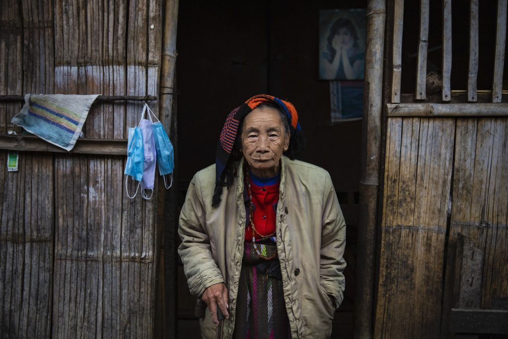 Nang Shen, a 90-year-old Kachin woman, at the entrance to her simple home in the KBC-1 camp for people displaced by conflict in Kutkai Township, northern Shan State. (Hkun Lat | Frontier)