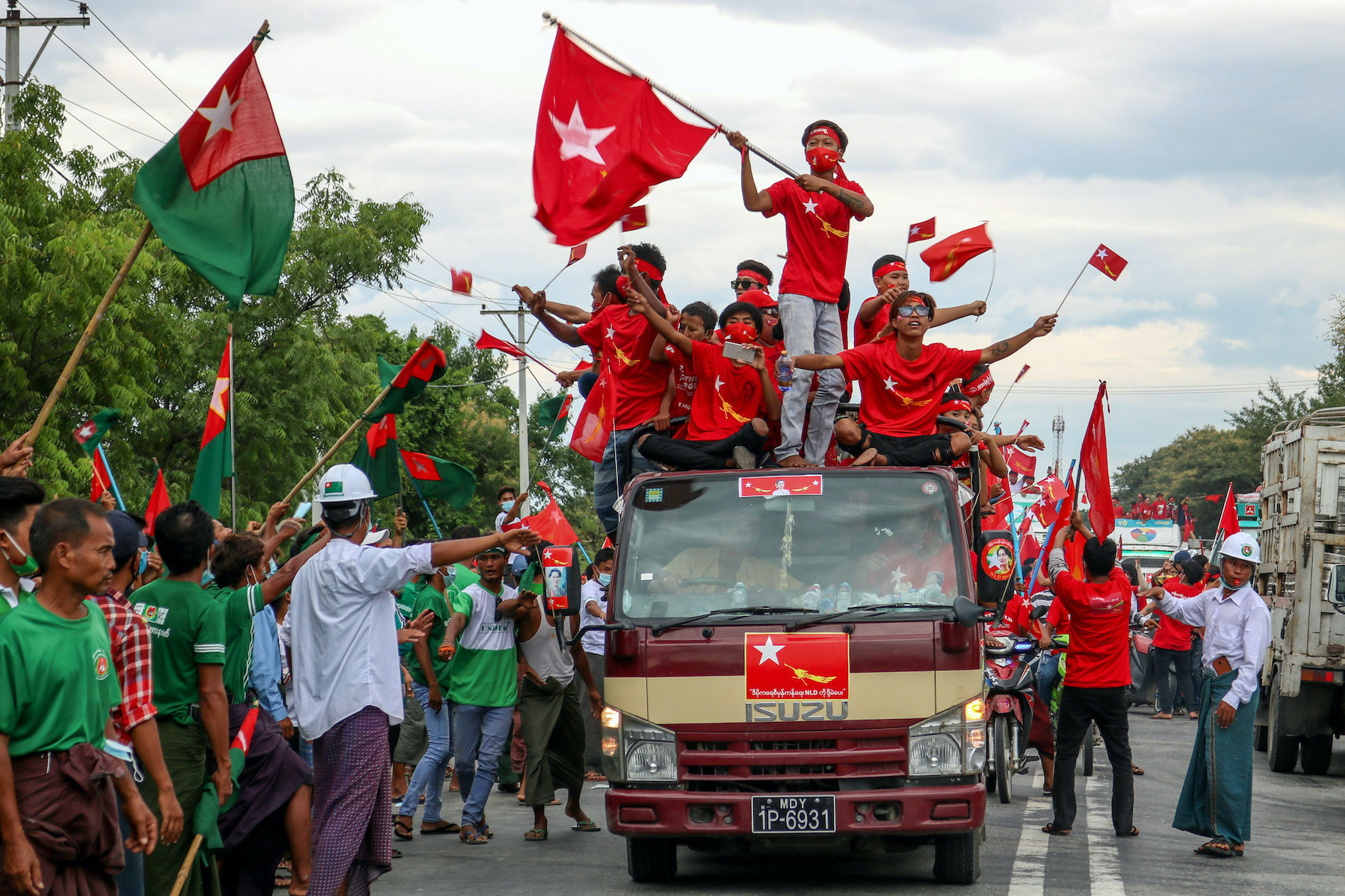 Supporters of the National League for Democracy party on a motorcade pass supporters of the opposition Union Solidarity and Development Party, left, during a campaign in Wundwin, near Mandalay on September 19. (AFP)