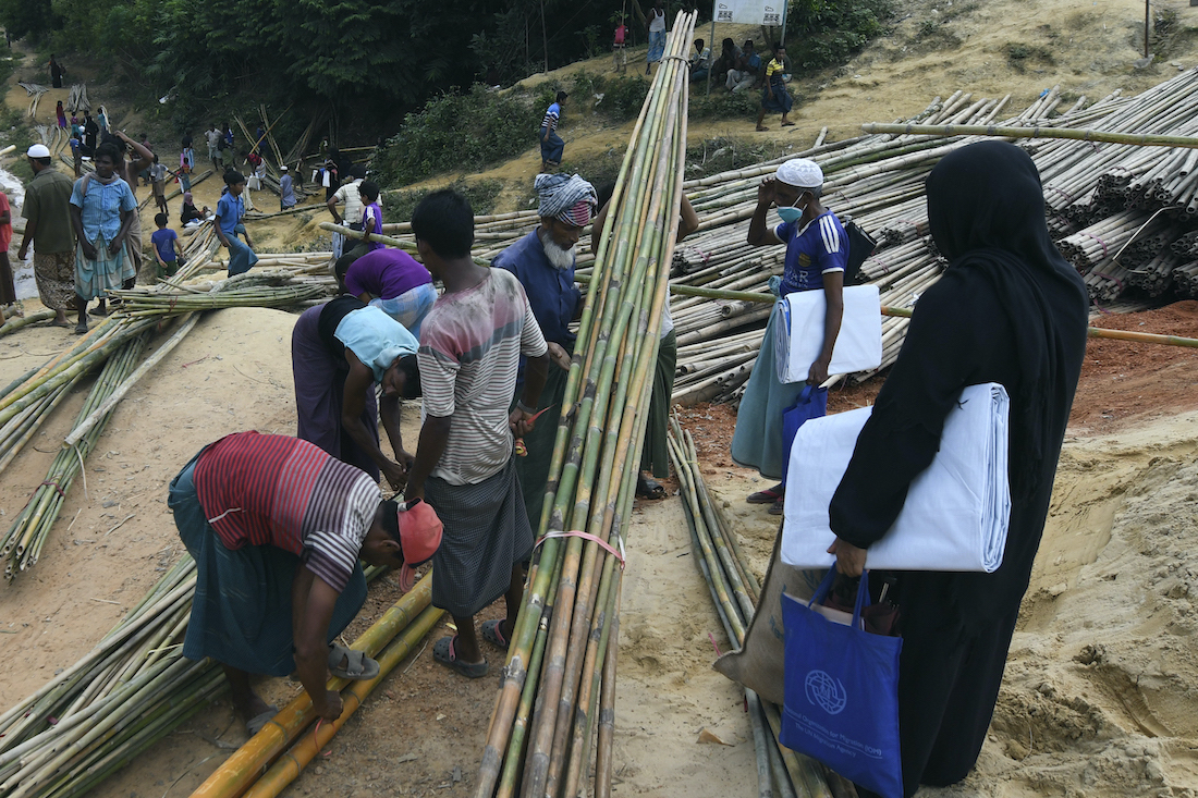 Rohingya refugees collect bamboo poles and other relief supplies at Kutupalong refugee camp in Ukhia on October 15. (AFP)