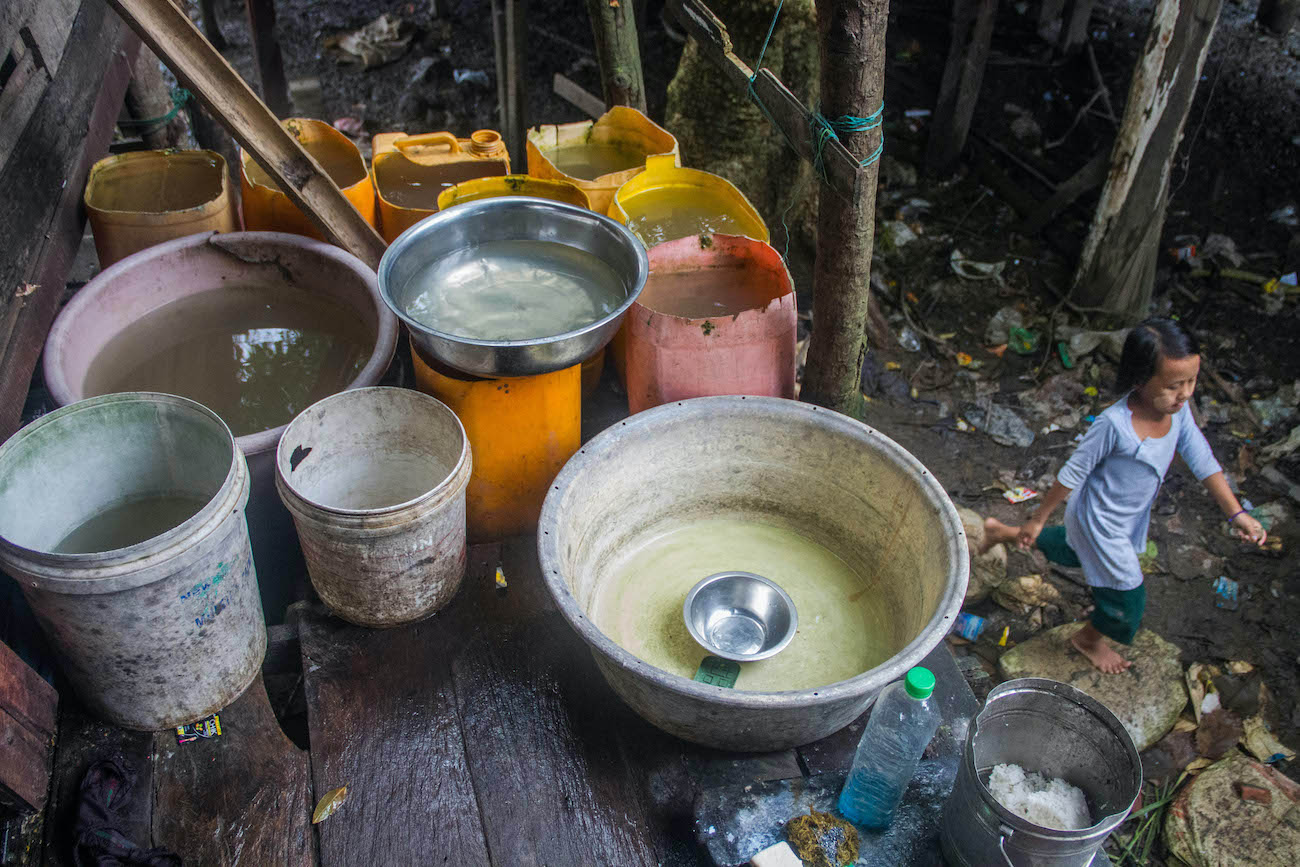 A household in Mawlawmyine's Lamuttan quarter uses bowls and buckets to store water. (Naw Betty Han | Frontier)