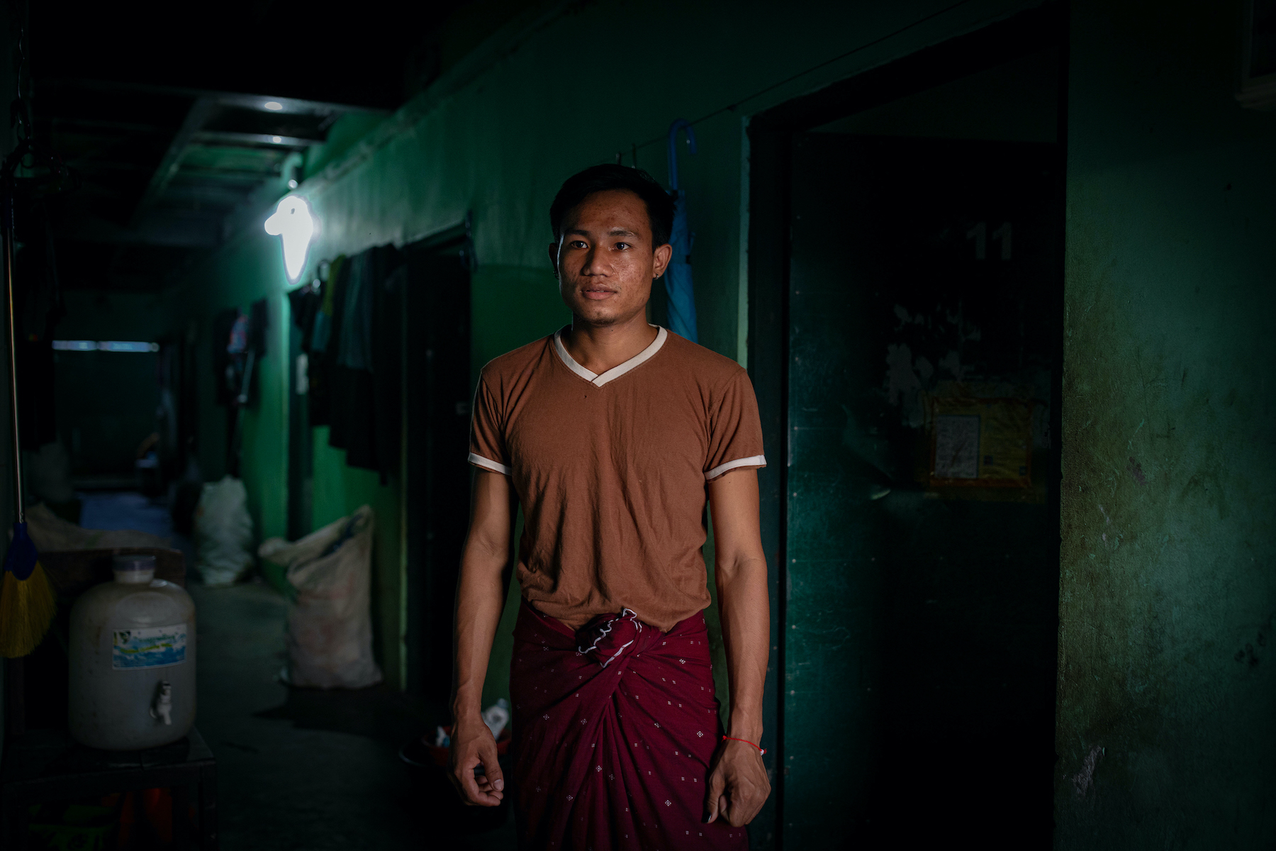 Factory worker Ko Thant Zaw Win stands in front of his dormitory room in Yangon's Hlaing Tharyar Township, which he shares with four other roommates, on October 26. Such cramped conditions, common in worker hostels across the overcrowded and industrial township,  have made factory shutdowns and stay-at-home orders harder to bear for laid-off workers, putting them at greater risk of mental health problems. (Hkun Lat | Frontier)