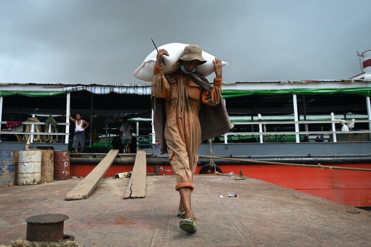 A worker unloads sacks of rice from a boat at the Yangon jetty on July 8. (AFP)