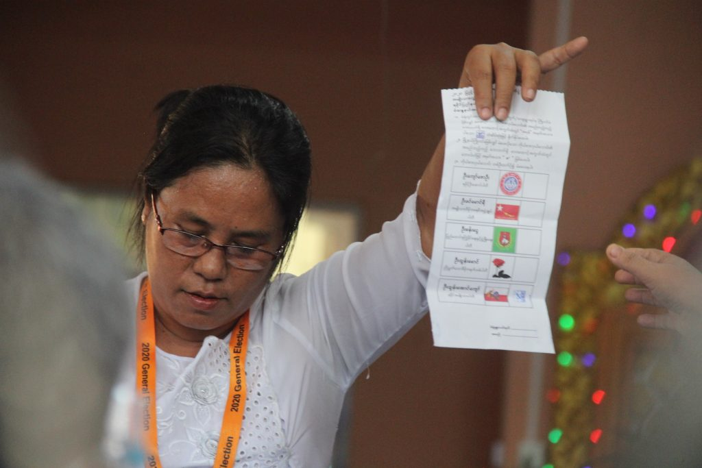 An election sub-commission official in Sittwe holds up a vote for the Arakan National Party. (Kaung Mratt Naing | Frontier)