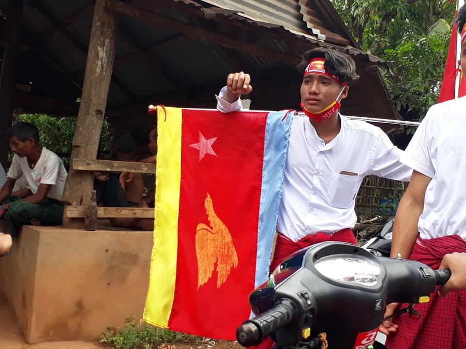 A young man campaigns with the flag of the Mon Unity Party in Mon State's Mudon Township on October 18. (Lawi Weng | Frontier)