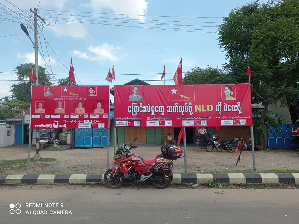 A motorcycle sits beneath signboards promoting the National League for Democracy in the southern Mandalay Region town of Pyawbwe – considered a stronghold of the opposition Union Solidarity and Development Party – in late October. (Supplied)