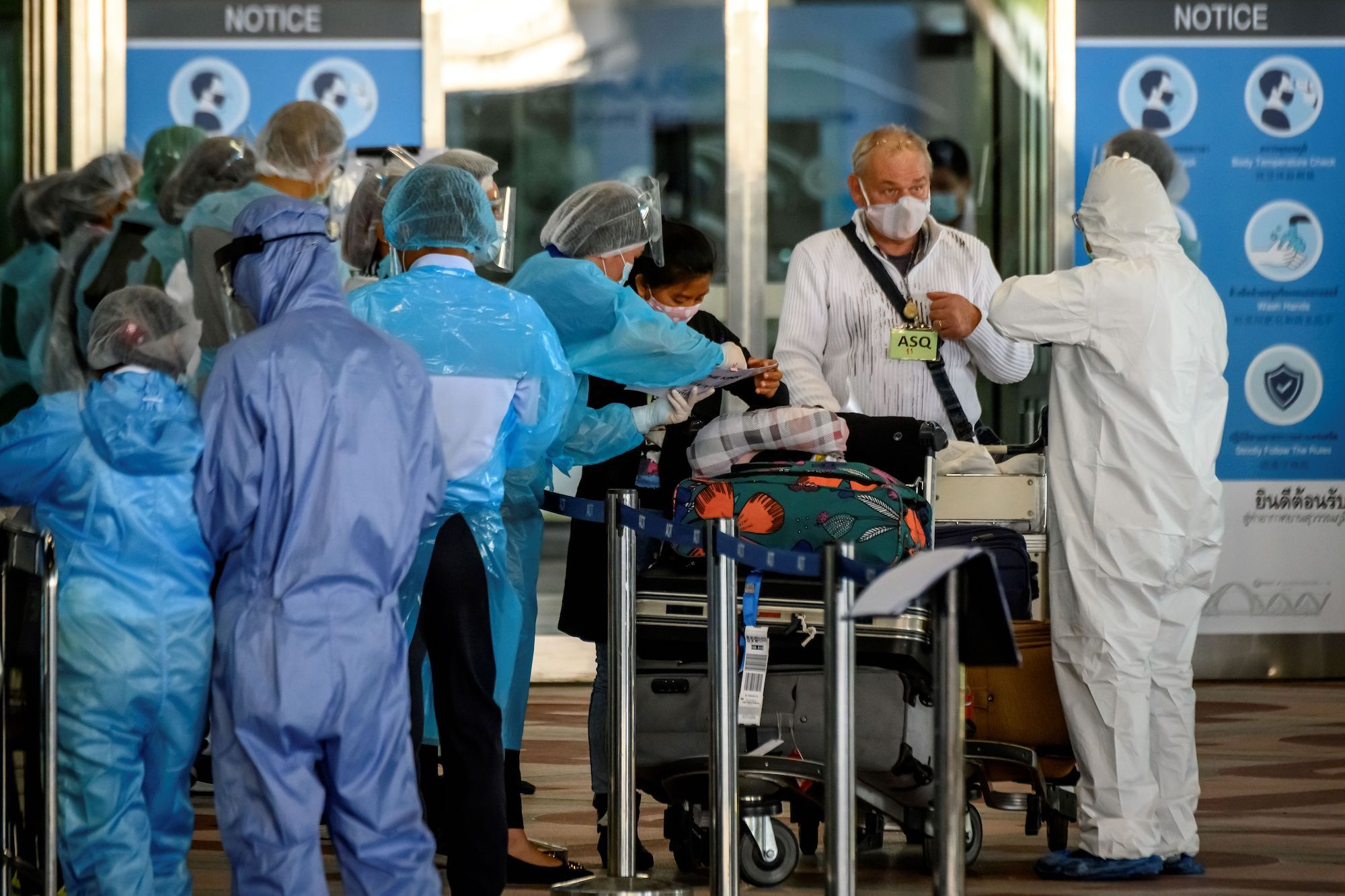 Employees in personal protective equipment at Bangkok's Suvarnabhumi Airport direct arriving international passengers to hotels for compulsory 14-day quarantines on November 16. The country has kept its COVID-19 case numbers low throughout the pandemic, but a cluster linked to Tachileik, Shan State, has Thai health authorities concerned. (AFP)