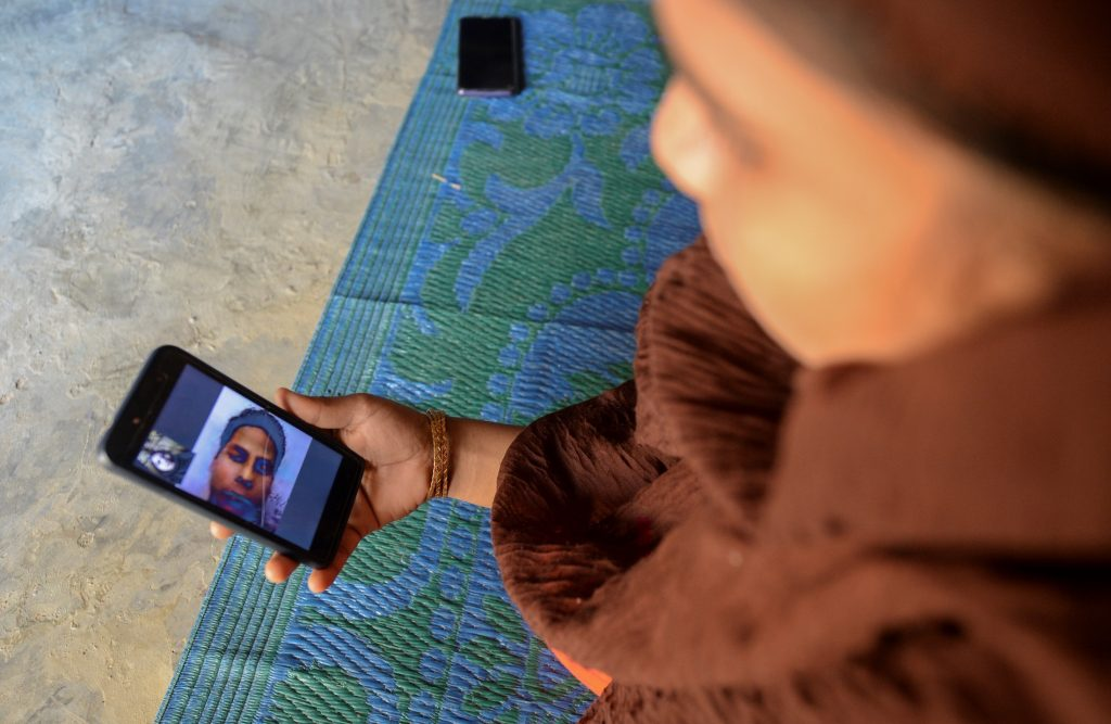 Rohingya refugee Umme Khair, who gave money to a community leader to travel to Malaysia to her husband, interacts with her spouse via video call at a makeshift shelter in Kutupalong Rohingya refugee in Bangladesh on October 13. (AFP)