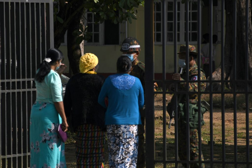 Members of the Arakan Women Network speak to soldiers outside of a military court in Sittwe, Rakhine State, on December 11, after a rare legal victory for a woman who was brutally raped by Tatmadaw soldiers. (AFP)