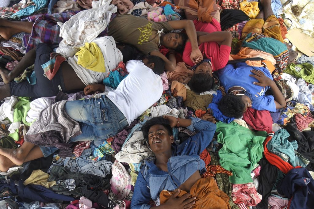 A group of Rohingya men travelling along a people smuggling route to Malaysia sleep on a pile of donated clothes on September 8, 2020, on the northern coast of Indonesia's Sumatra island. (AFP)