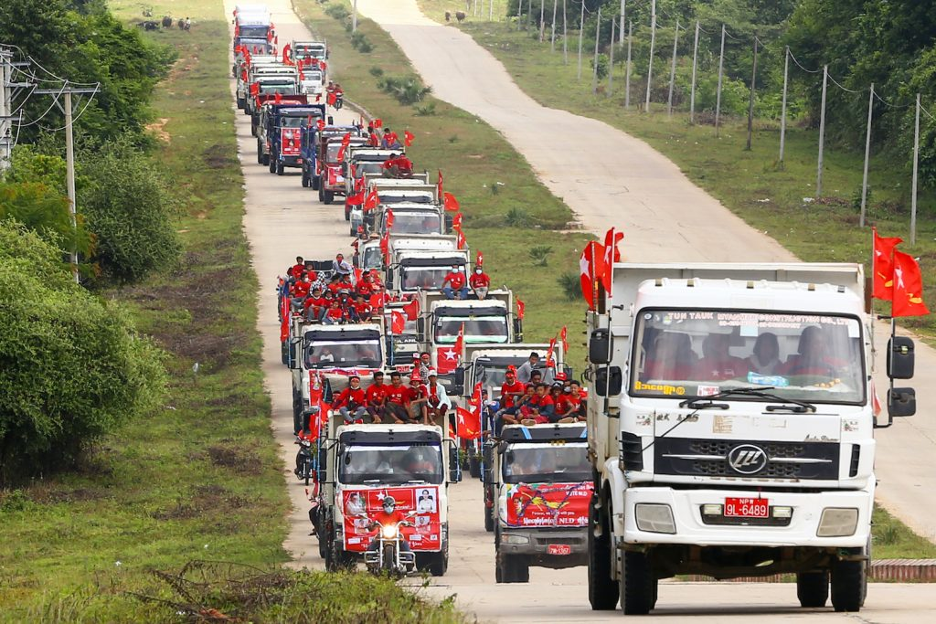 National League for Democracy supporters ride in trucks during a campaign rally in Nay Pyi Taw on October 21. (Thet Aung | AFP)