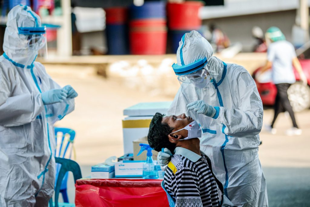 Medical officials test a man for the COVID-19 at a seafood market in the migrant hub of Samut Sakhon on December 19, two days after the virus was detected in a worker from Myanmar. (AFP)