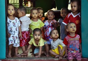 Children peer out from a doorway at the Yellow Generation Wave Monastery in Yangon Region. (Steve Tickner | Frontier)
