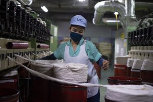 A Myanmar migrant worker handles barrels of cotton in a textile factory in Pathum Thani Province, Thailand. (AFP)