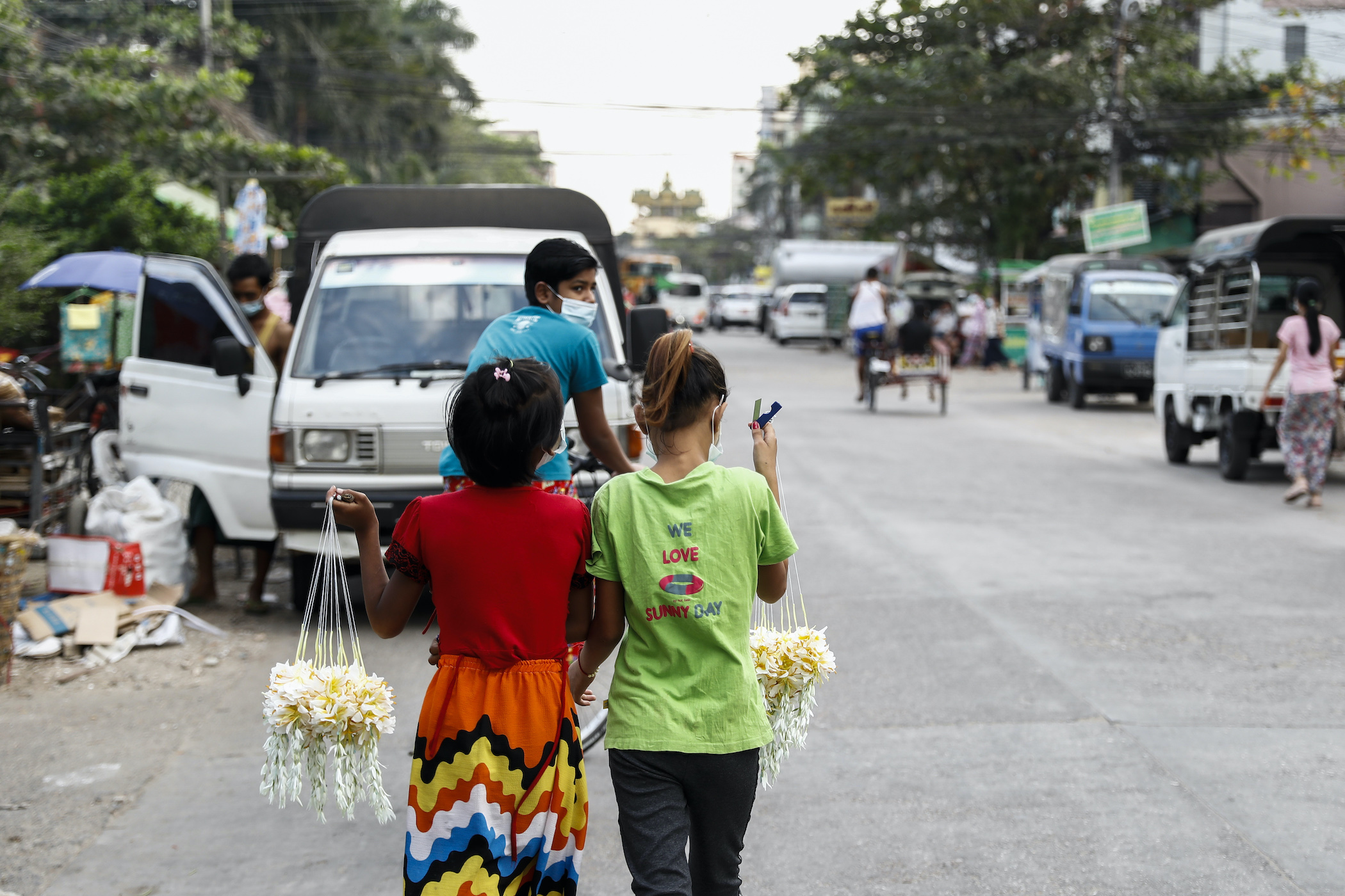 Two young girls sell flowers to support their families in Yangon on December 21. (Nyein Su Wai Kyaw Soe | Frontier)
