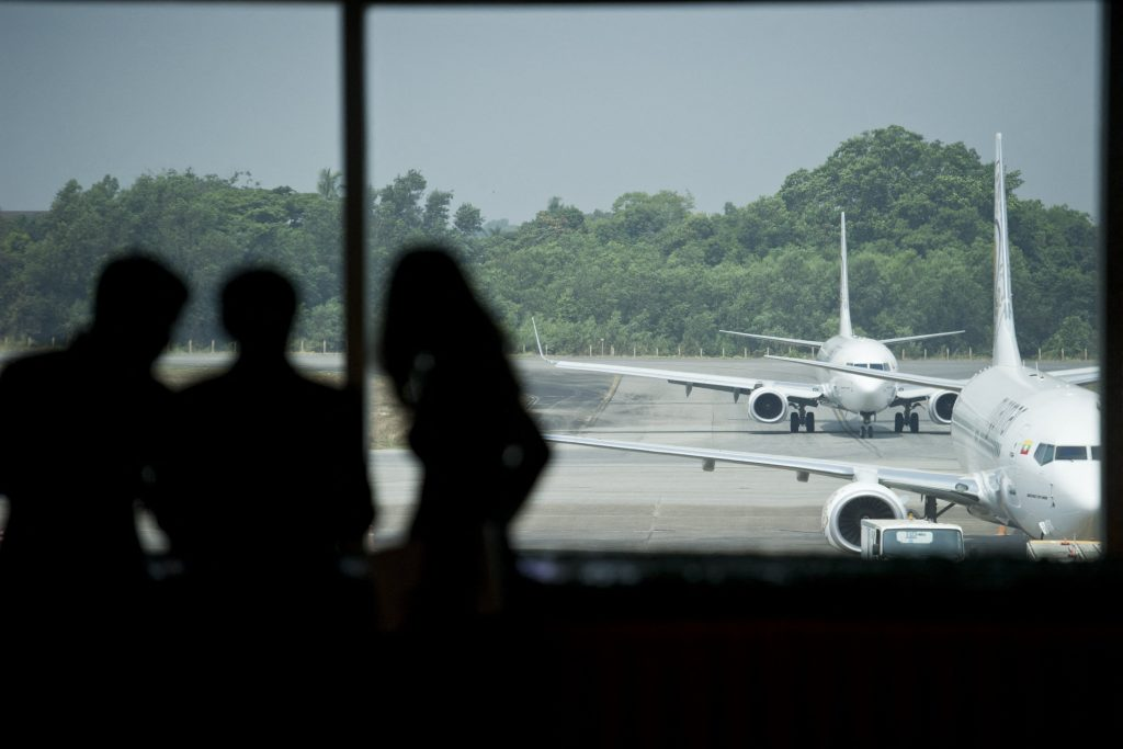People look on as aircraft are seen from the window of a terminal at Yangon International Airport. (AFP)