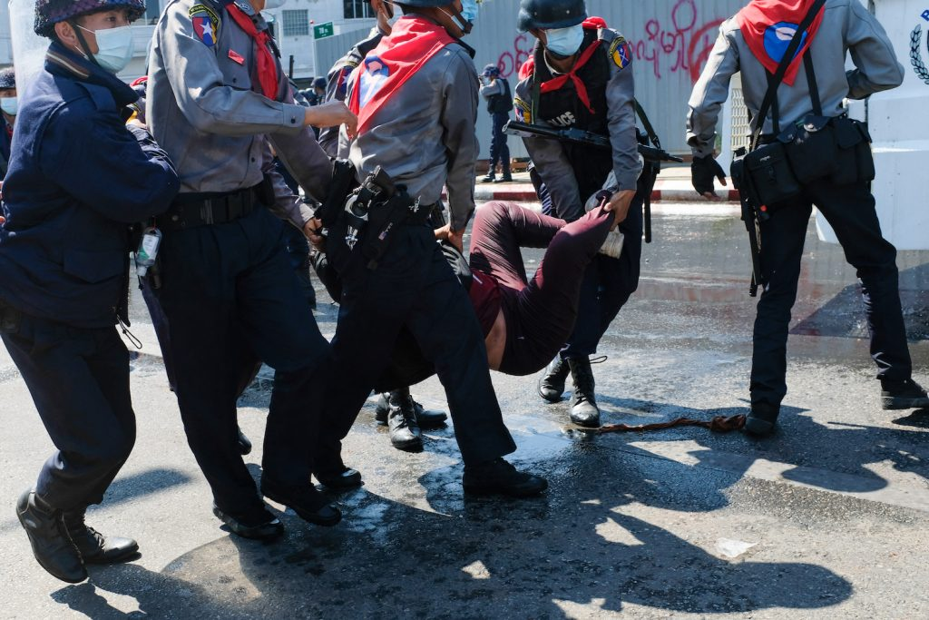 Police carry a protester as they arrest her during a demonstration against the military coup in Mandalay on February 9, 2021. (AFP)