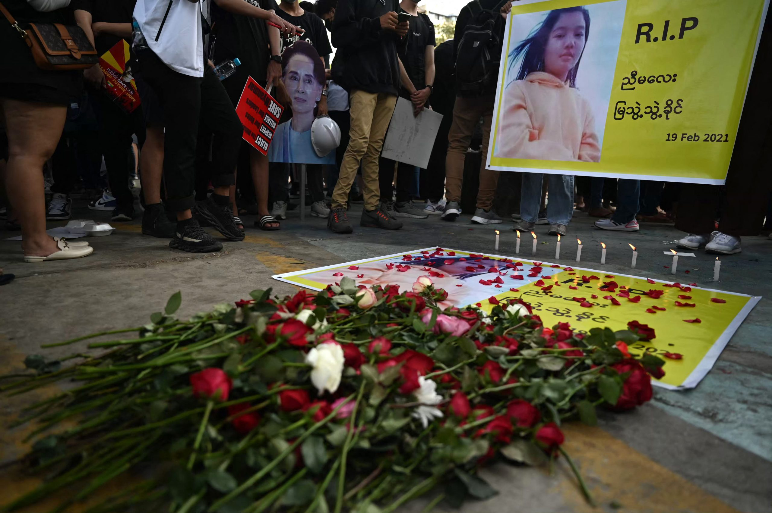 Flowers are placed next to a banner during a memorial for Ma Mya Thwate Thwate Khaing in Yangon on February 20. The young woman died from a gunshot wound sustained during a rally against the military on February 9. (AFP)