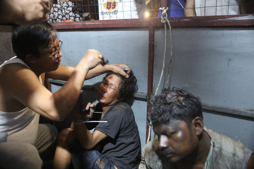 A Yangon resident shaves the eyebrows and head of a man detained by locals in Botahtaung Township after curfew on February 13. Residents suspected the man and two others caught the same night had been sent to cause mayhem in the neighbourhood but there was little evidence to support this allegation. (Frontier)