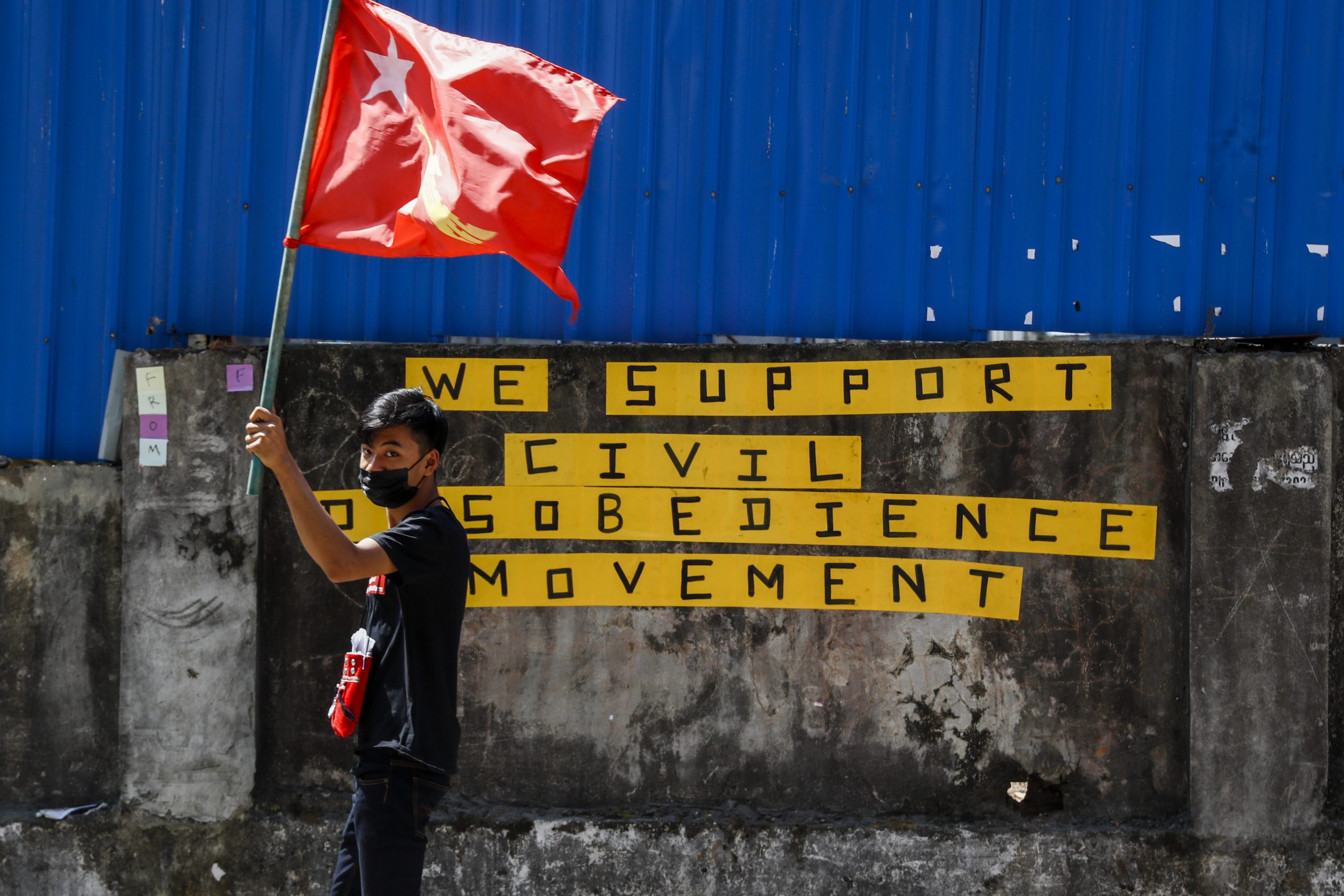 A protester waves a National League for Democracy flag in Yangon. (Frontier)