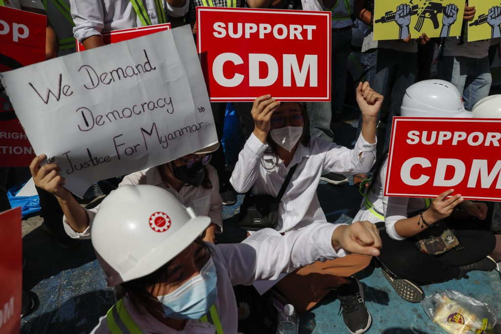 Protesters in Yangon hold placards urging the public to support the Civil Disobedience Movement on February 25. (Frontier)