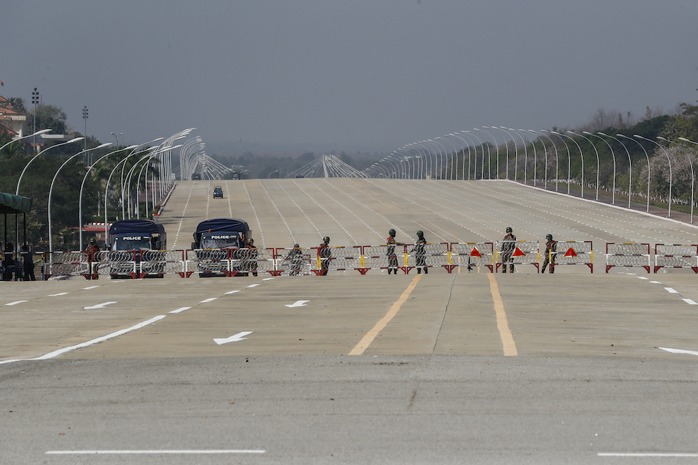 Police and Tatmadaw soldiers erect a barricade across a major road in Nay Pyi Taw on February 2. (Frontier)